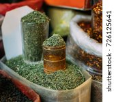 Small photo of Tbilisi, Georgia. Close Full Glass And Tray Of Crushed Dried Rosemary Leaves, Popular Spice Of Fragrant Bitter Astringent Taste And Aroma For Sale At Showcase Of East Market, Bazaar.