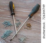 Small photo of Two adjacent screwdriver and screws of various sizes