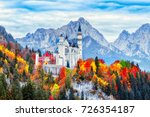 Neuschwanstein medieval castle in Germany, Bavaria land. Beautiful autumn scenery of Neuschwanstein ancient castle circled by colorful tree, amazing seasonal fall scene. Famous and popular landmark.