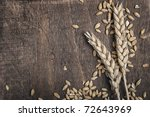 Wheat ears on an old wooden plank - stock photo