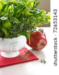 Green salad in a white porcelain bowl and red apple. - stock photo
