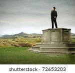 Businessman standing on a pedestal on a green meadow - stock photo