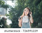 Small photo of Woman walk in the park outdoor and listening to the music media entertainment. Relaxation concept. Soft picture for feeling relax with easy listening music.