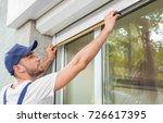 man measuring window prior to...   Shutterstock . vector #726617395