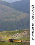 Small photo of mountain landscape with cog railway steam train slowly driving up the mountain