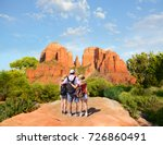 Father with arms around his family  looking at beautiful summer mountains landscape. People on hiking trip enjoying view of  Cathedral Rock, Sedona, Arizona, USA
