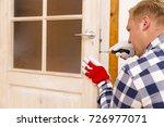 handyman fixing the door with... | Shutterstock . vector #726977071