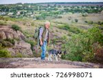 Stock photo tourist man with a gray beard with his dog breed of husky against the backdrop of trees gorges and 726998071
