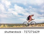 Small photo of Triathlon cyclist biking on road bike on ironman competition racing against time on nature background landscape. Copy space above athlete on sky.