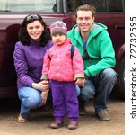 Small photo of Family, mother, father and child, in outwear hunker down in front of car and smile