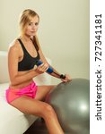 Small photo of Sport, training, gym and lifestyle concept. Young attractive slim woman in sportswear with air pump inflating fit ball, fitness exercise