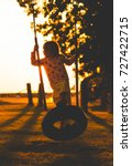Small photo of girl swinging in sunset. kid playing with tire handmade swing in the evening.