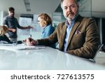 mature businessman sitting in... | Shutterstock . vector #727613575