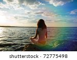 girl meditations in sunrays near water - stock photo