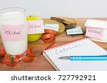 Small photo of Counting calories, different food with written quantity of calories, diet concept.