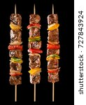 Small photo of Meat skewer with vegetables on a black background. Paulistinha.