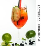 Small photo of Alcoholic beverage and currant berry at restaurant. Party and summer vacation. Cocktail with blueberry isolated on white background. Drink and food. Drinking straw in cocktail glass with lime at bar.