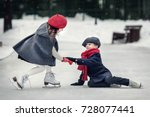 On the skating ring. Girl in red beret is helping falling boy to stand up. Image with selective focus and toning.