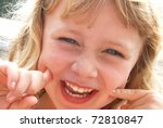 Cute girl making a funny smiling face for the camera. - stock photo