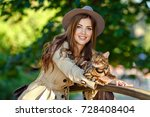 Stock photo a very beautiful fashionable girl with a brown haired hat in the hands of a bengal cat in a green 728408404