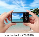 Tourist's hands holding digital photo camera on vacations, taking picture of beautiful sunny seaside - stock photo
