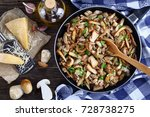 Small photo of Funghi trifolati or fried porcini sprinkled with parsley in skillet with kitchen towel on old dark wooden table with fresh whole ceps, parmesan cheese and olive oil, view from above, close-up