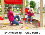 Small photo of Conflict on the playground. Two sisters fighting over a toy shovel in the sandbox. Kid sister crying all throat