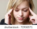 A young woman relieves the pain from her headache by putting pressure on her temples. - stock photo