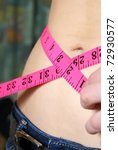 A woman measures her waistline to account for her ideal size and fitness. - stock photo