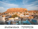 The color of the residential structures at the base of Mehrangarh Fort give Jodhpur its nickname, the Blue City.  Horizontal - stock photo