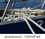 Small photo of Details of mooring lines positioned through a stainless steel fairlead and anchor chain on a sailing boat. Horizontal view.