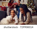 Stock photo happy smiling sisters are playing with dog they are lying on floor near christmas tree 729908314