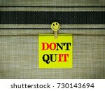 """Small photo of Motivational quote """"Don't quit"""" on sticky color note."""