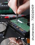 Small photo of Hard disc drive disassembling close up. Repairman opening hdd for recovery information, service center and electronics repair concept.