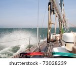 Sailing boat sailing in the stormy sea at sunny day - stock photo