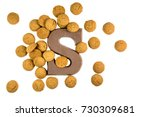 Small photo of Handful of Pepernoten cookies or ginger nuts with chocolate letter as Sinterklaas decoration on white background for dutch sinterklaasfeest holiday event on december 5th
