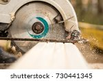 Small photo of worker saws a wooden plank at a construction site