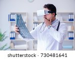 young doctor looking at mri... | Shutterstock . vector #730481641