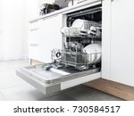 Open dishwasher with clean dishes in the white kitchen - stock photo