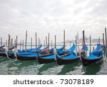Gondolas with blue cover in Venice at the pier - stock photo