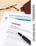 Small photo of Resume and employment application form with glasses and neck tie