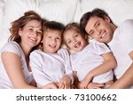 smiling family in bed   Shutterstock . vector #73100662