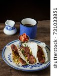 Small photo of Breakfast tacos with kielbasa sausage tacos, eggs and cilantro on a vintage plate and rustic background