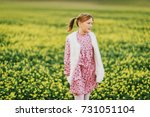 Small photo of Outdoor portrait of pretty 10 year old girl, wearing pink vintage dress and faux fur bodywarmer, posing in a field