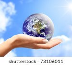 Globe In Human Hand Against...