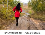 girl in a red coat walking on a ... | Shutterstock . vector #731191531