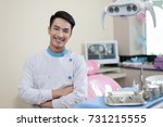 male dentist crossing arm while ... | Shutterstock . vector #731215555