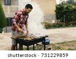 handsome man preparing barbecue ... | Shutterstock . vector #731229859