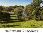 autumn garden by a pond | Shutterstock . vector #731290351