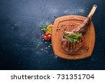 steak on the bone. top view.... | Shutterstock . vector #731351704